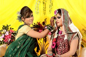 Relatives decorating the bride with traditional wedding turmeric in a Bangladeshi Gaye Holud ceremony in Dhaka.