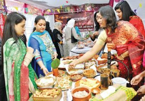 Visitors are testing different types of pitha at a Pitha Utshob.